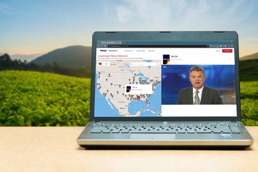 A news livestream displayed on a laptop outdoors.