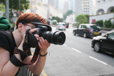 Woman shooting a DSLR in the city