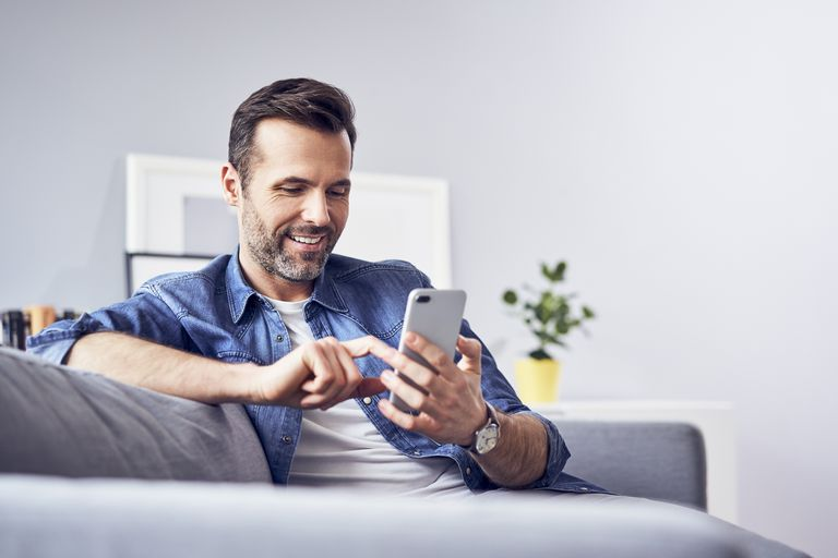 Man sitting on sofa using cell phone.