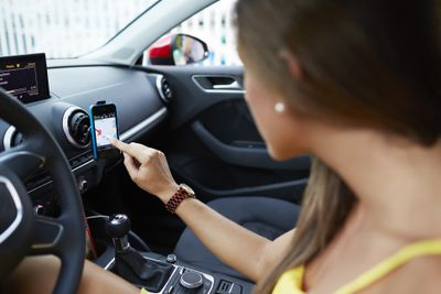 Person using smartphone as GPS navigation in car