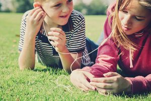 Two children lying on grass listening to music through a smartphone