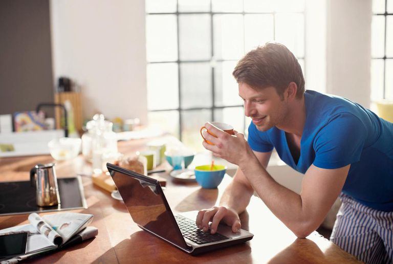 Man using laptop with cup of coffee