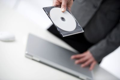 Person holding a CD and laptop