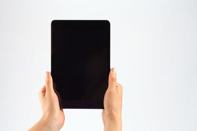 Cropped Hands Of Person Holding Digital Tablet Against White Background