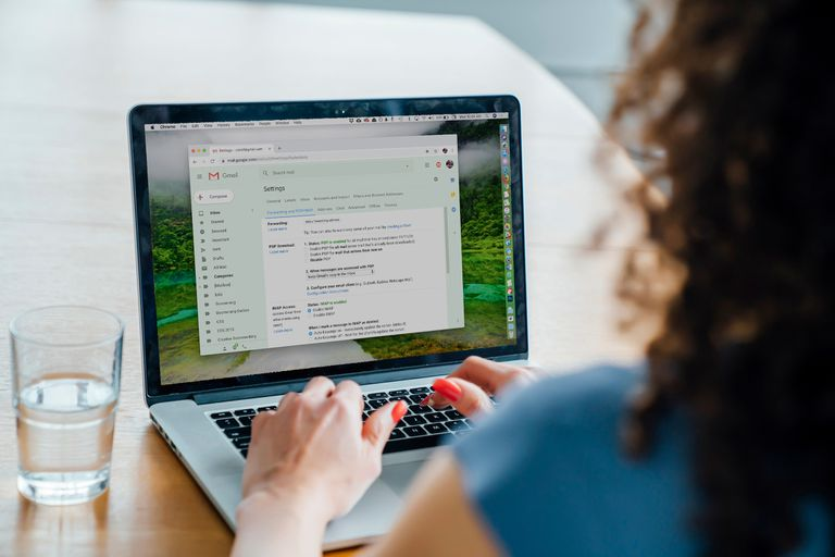 Woman setting her Gmail forwarding setting on a Macbook