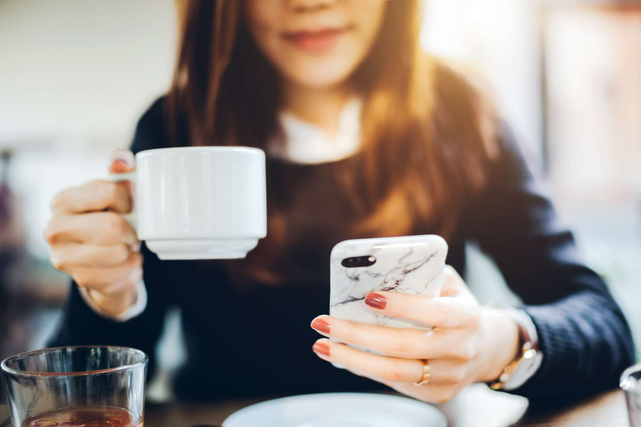 woman drinking coffee and checking email on phone