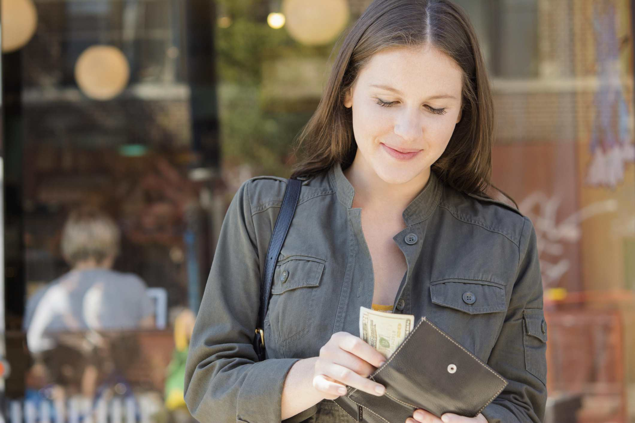 Image of a woman pulling money out of her wallet.
