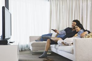 A couple sitting on a couch smiling watching TV