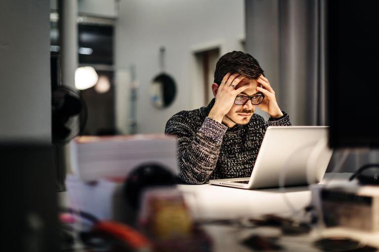 Figure 1-1: A young business man with his hands to his forehead contemplating a problem.
