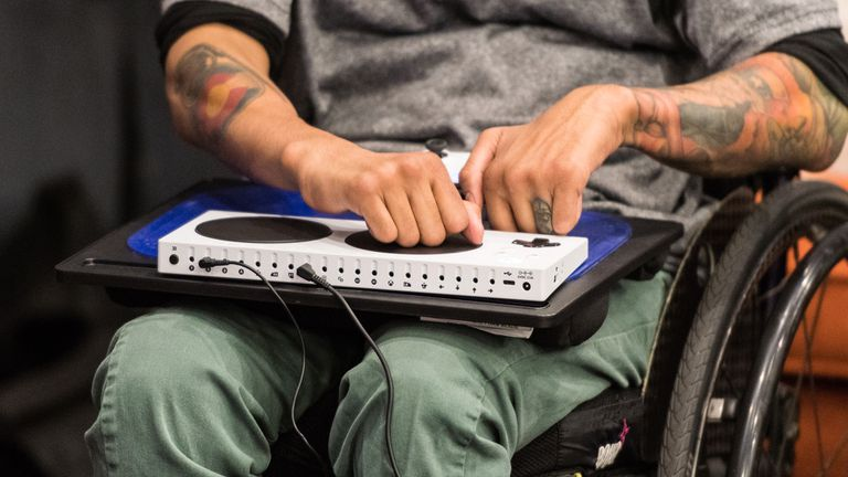 A man in a wheelchair using the Xbox Adaptive Controller.