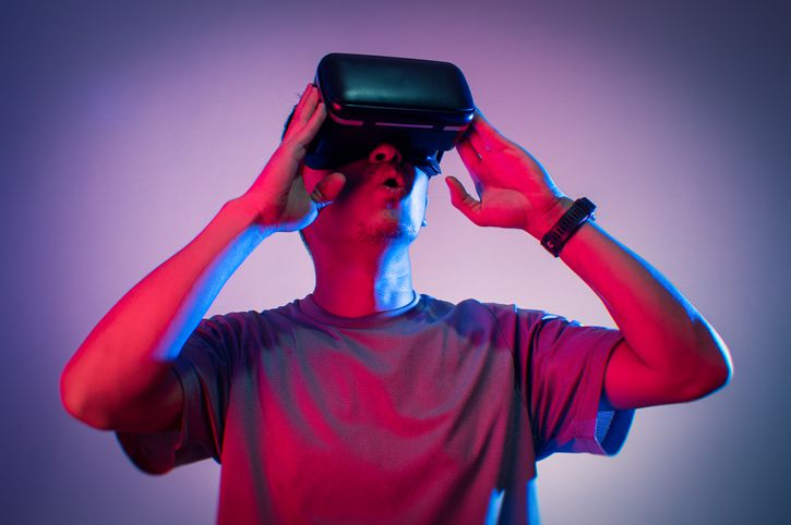 man playing VR goggle with colorful lighting