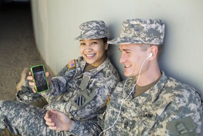 Active duty military members relaxing with their phone and music.