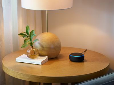 An Amazon Echo Dot on a charcoal table