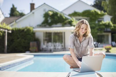 Woman using laptop on diving board at poolside