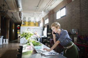 Florist working at laptop in flower shop