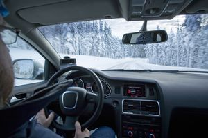 Person driving SUV in snow covered road in a forest