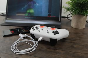 A Stadia controller with a earbud headset plugged in and Cyberpunk 2077 in the background.