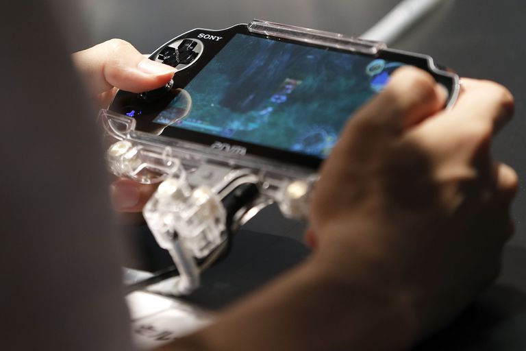 Close up of person playing PS Vita in person's hands