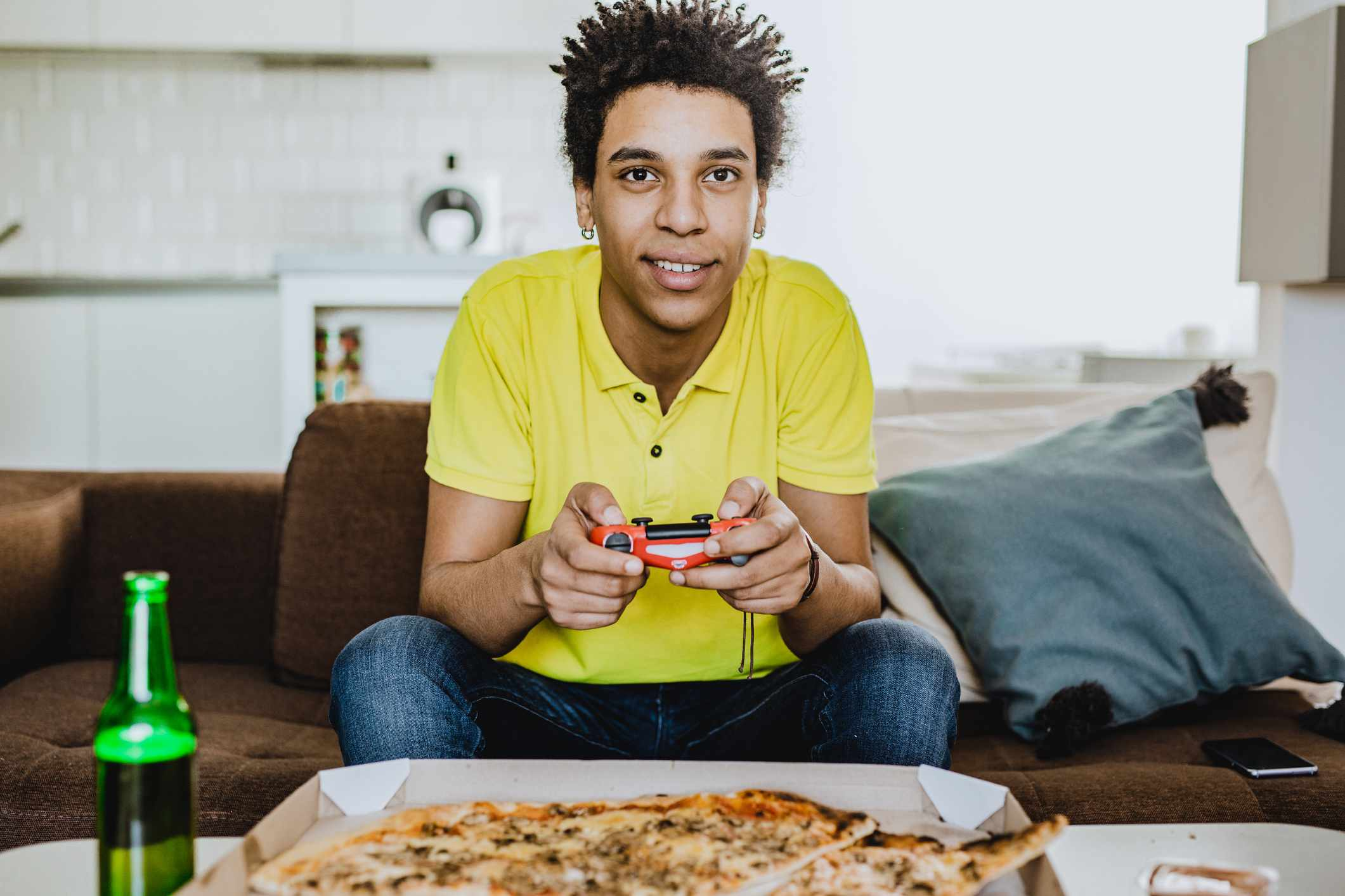 A young adult playing video gamers over a pizza and a drink.