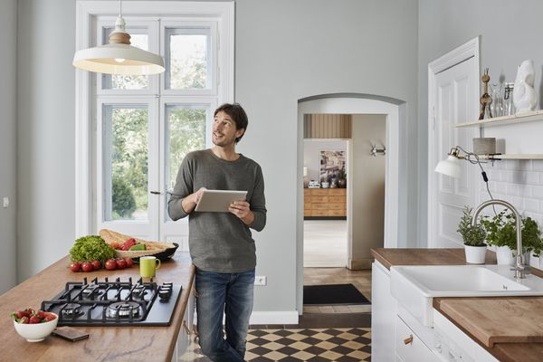 A man standing in a kitchen looking at a ceiling light while holding a tablet