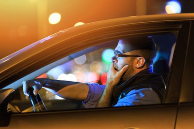 A drowsy driver who could benefit from a driver alert system yawns in his car.