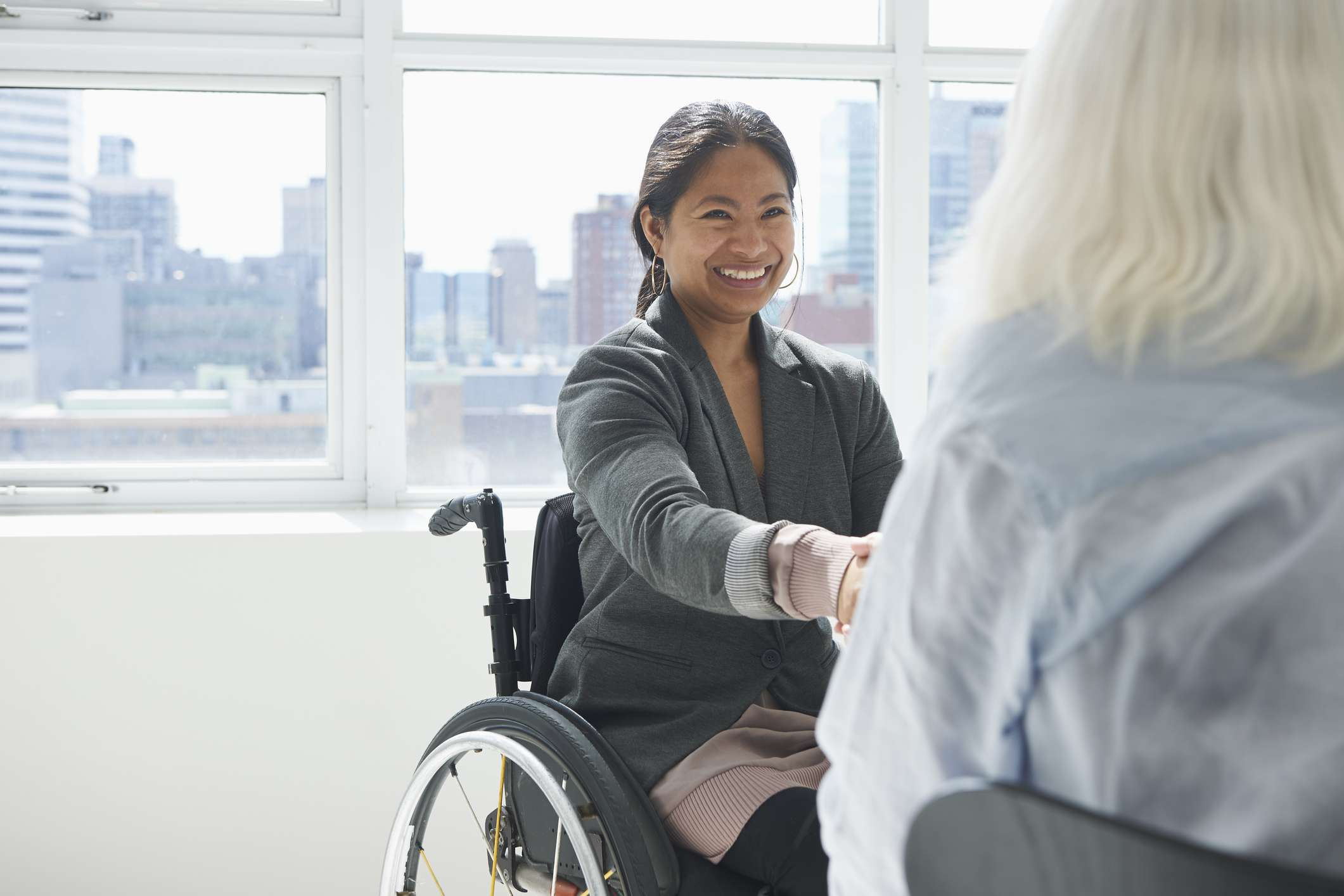 Businesswoman in a wheelchair shaking hands with another person