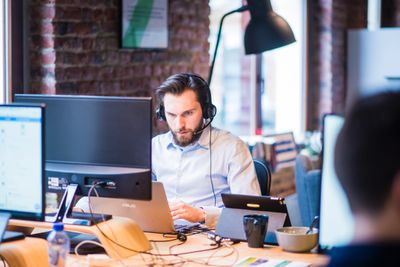 Man working on office desk with laptop and large monitor