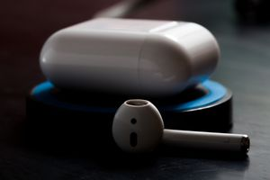 Apple AirPods resting on a wireless charging base