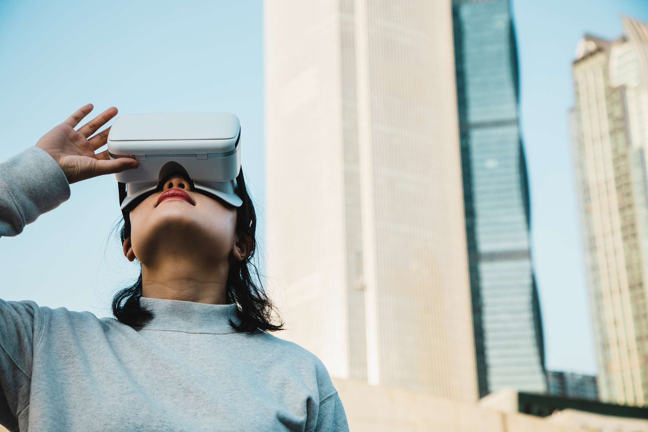 Woman using Virtual Reality headset in the city
