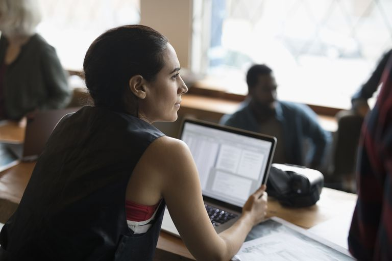 Serious female computer programmer working at laptop in meeting