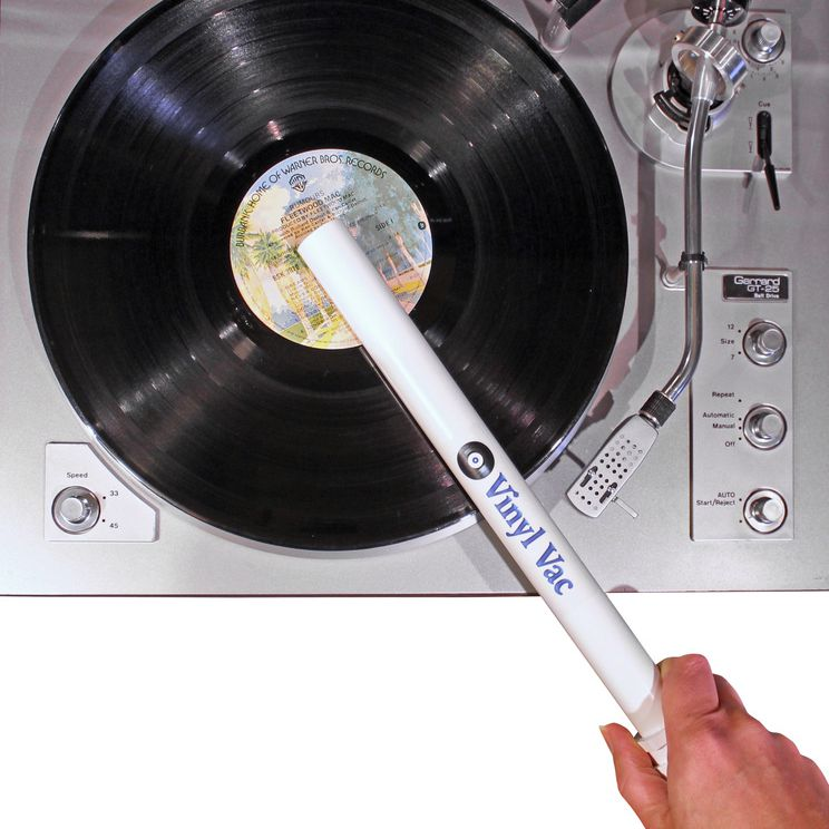 A hand holding a Vinyl Vac to clean a record lying on top of a turntable