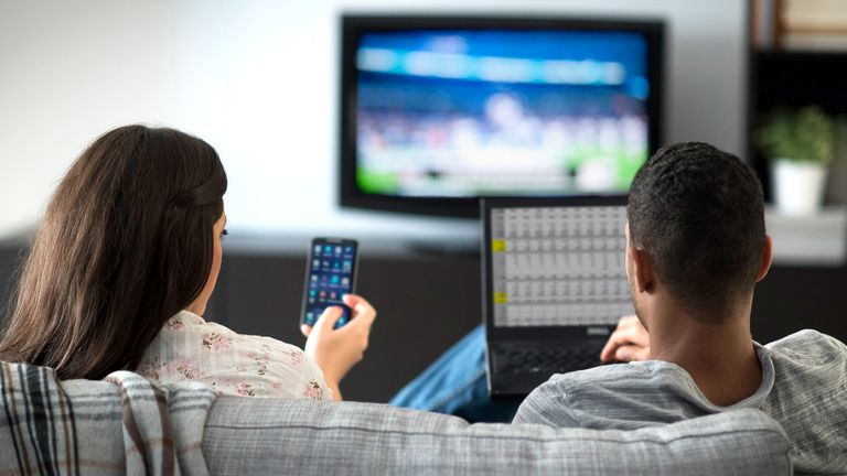 Male and female college students streaming media from their iPhone and laptop to their dorm room TV