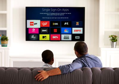 A father and son sitting on a lounge looking at a TV with AT and T cable provider single sign on apps on a Fire TV Stick.