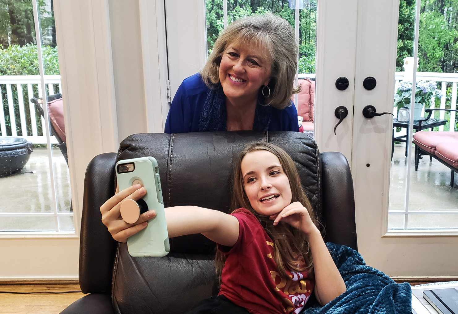 A young person snapping pictures with a grandparent, using the PopSocket on the phone to hold it in place.