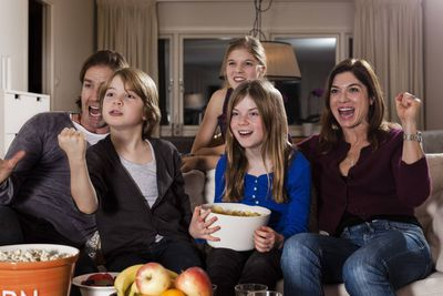 A picture of a family watching a movie at home