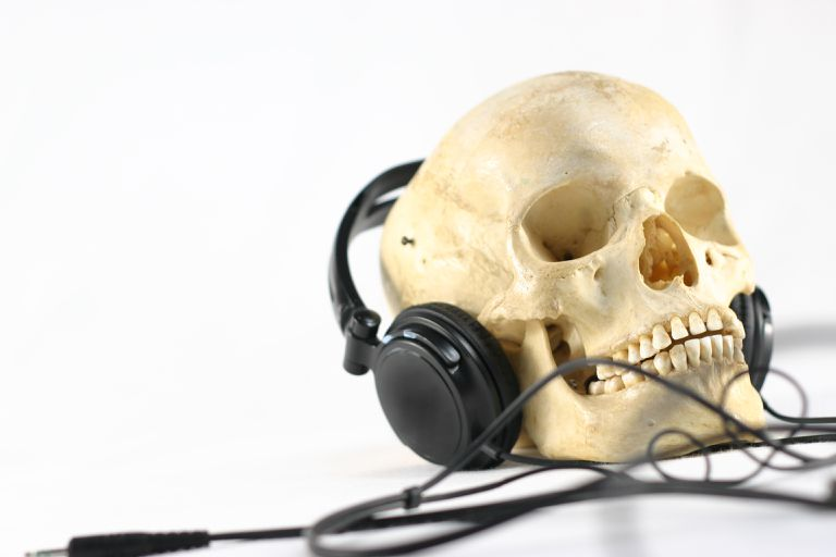 A skull listening to Halloween music through headphones
