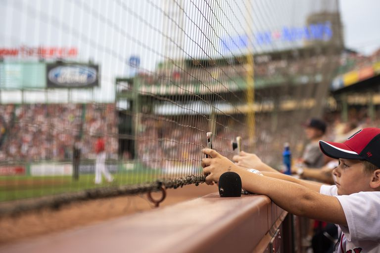 A young baseball fan, using his phone while sitting behind the netting at a baseball game