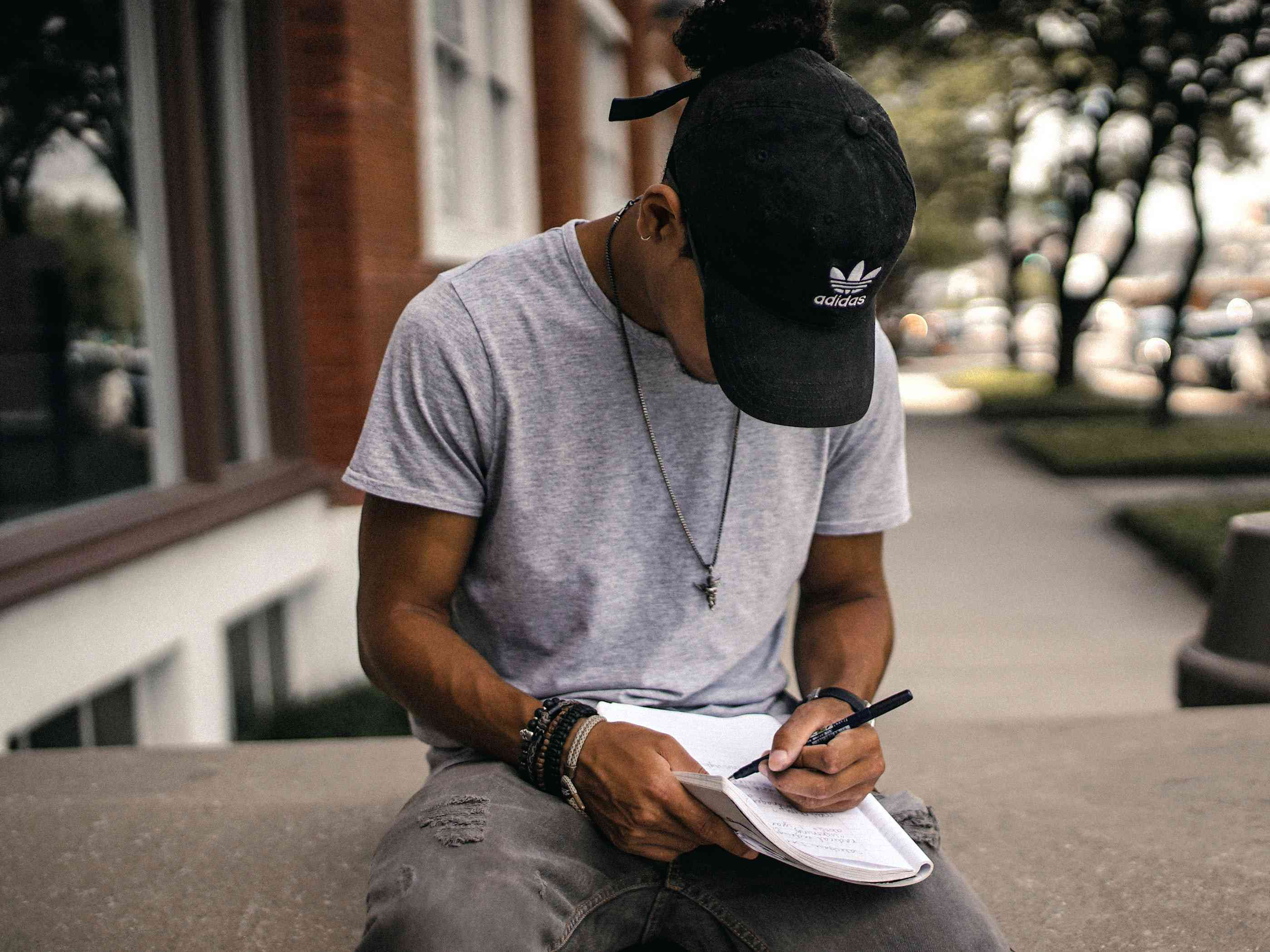 person sitting on a bench writing in a notebook