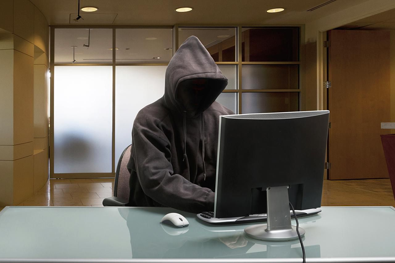 Hacker in a hooded sweatshort sitting in front of a computer
