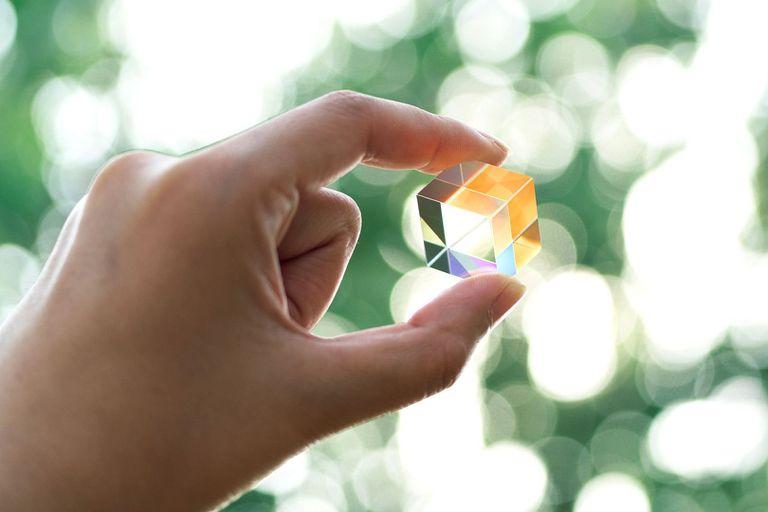 A human hand holding up a transparent glass gem
