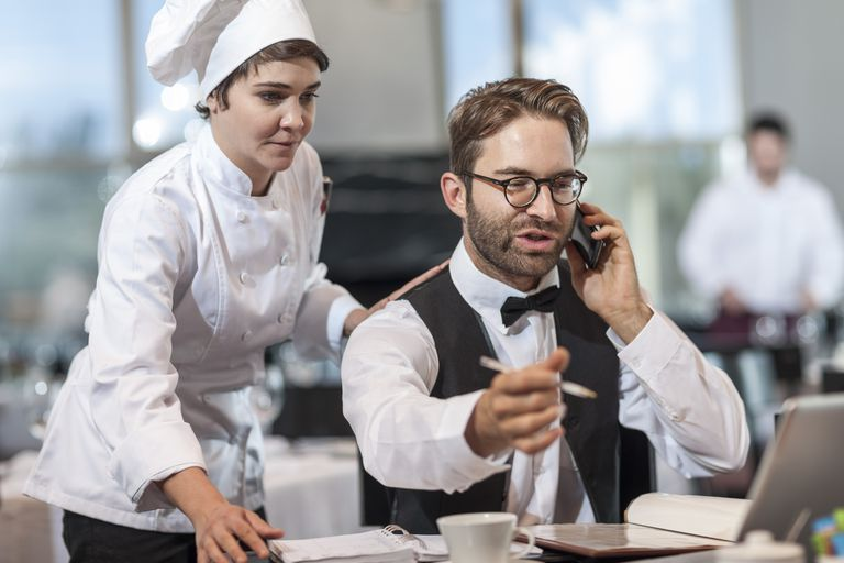 Restaurant chef standing behind a manager as they take a phone reservation.