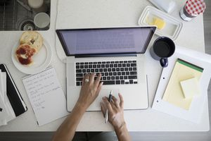 Photo of woman typing on a laptop surrounded by notepads