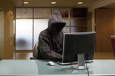 Hacker in a hooded sweatshirt sitting in front of a computer
