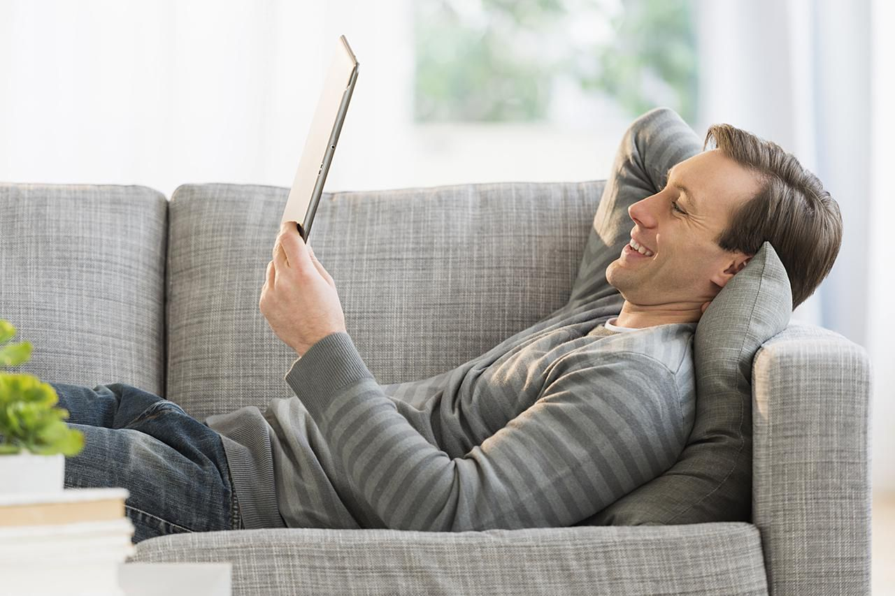 Person lying on couch looking at tablet.