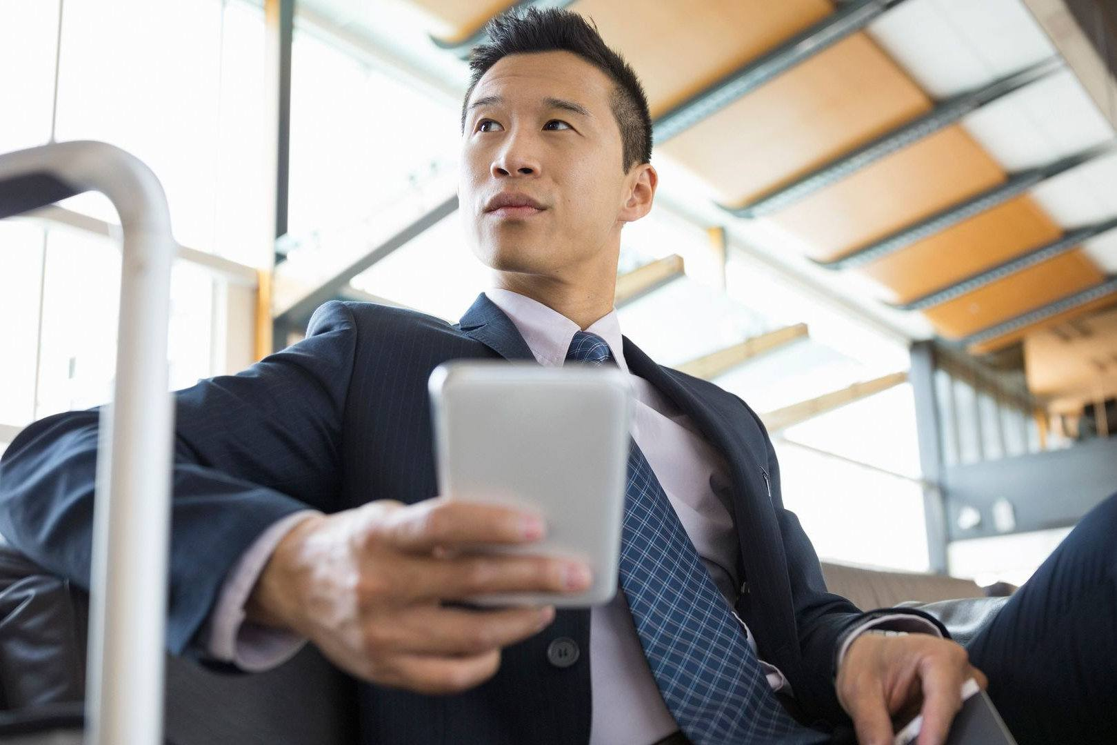 Businessperson on a business trip checking an iPhone on a train