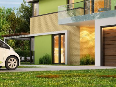 Electric car charging in driveway of a modern home.