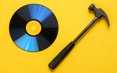 Photo of a CD disc and a hammer on a yellow background.