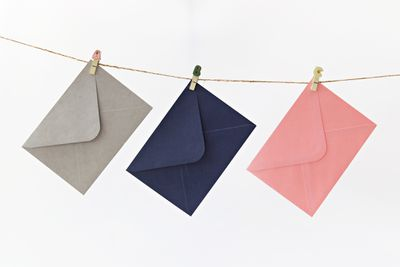 Close-Up Of Envelopes Hanging On Clothesline Against White Background