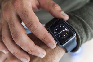 Hand pressing digital crown on Apple Watch
