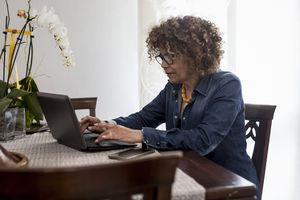 A person typing on a laptop at the kitchen table in their home.